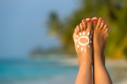 Woman's Foot With Sun-shaped Sun Cream In The Tropical Beach Conceptual Image Of Vacation